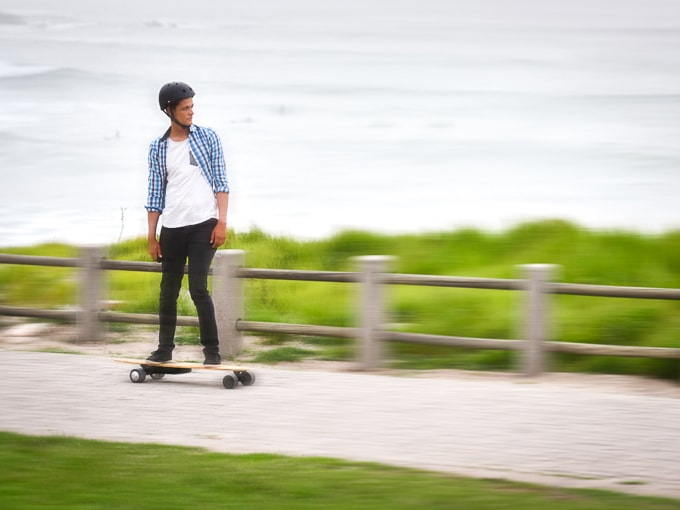 A skateboarder testing how fast an electric skateboard can go, with the ocean in the background