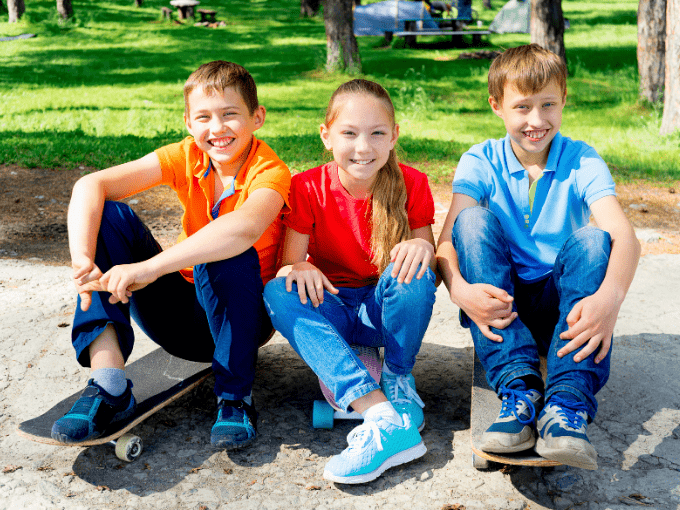 Three kids with electric skateboards